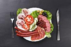 A carne, hamon, salsicha corta a variedade na placa com colher e k Foto de Stock