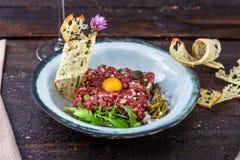 Carne a la tártara deliciosa con la yema de huevo, las alcaparras, la cebolla verde y el pan Fotografía de archivo