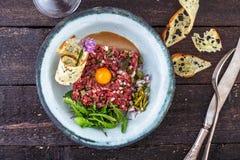 Carne a la tártara deliciosa con la yema de huevo, las alcaparras, la cebolla verde y el pan Imagen de archivo