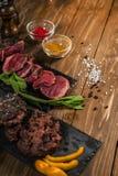 Carne, menta, hamburguesas asadas a la parrilla, en una tabla de madera fotos de archivo libres de regalías