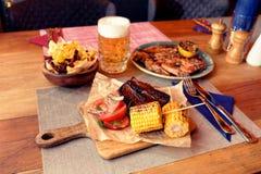 Carne, milho, microplaquetas de batata grelhadas e cerveja, tonificados fotos de stock