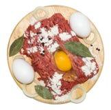 Carne moída com ovos em uma placa de corte Fotografia de Stock Royalty Free