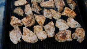 A carne na grade na cozinha do restaurante, muita carne madura nos bifes fritou em uma grade da frigideira no video estoque