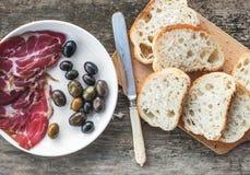 Carne o prosciutto di Parma ed olive affumicati su un piatto bianco, coltello d'annata, fette delle baguette sopra fondo di legno Fotografia Stock Libera da Diritti