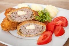 Carne panada e fritada, servida com batata e tomate fotografia de stock