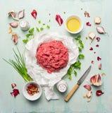 Carne picadita con cocinar los ingredientes, el aceite, las hierbas y las especias en fondo de madera azul Fotografía de archivo