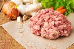 Carne picadita cruda fresca en la tabla de madera, con las verduras Imágenes de archivo libres de regalías