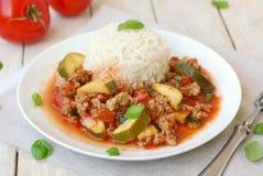 Carne picado picante con los tomates, la albahaca y el calabacín con el arroz basmati Fotos de archivo libres de regalías