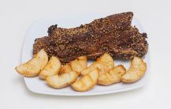 Carne picante grelhada com a batata na placa branca Imagem de Stock Royalty Free