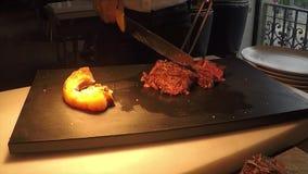 A carne profissional do bife do beaf cortou o servise com equipamento especial e as mãos das mulheres em uma cozinha preta embarc vídeos de arquivo