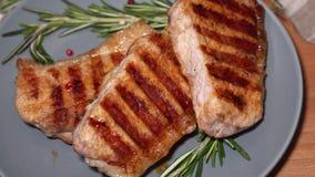 Carne quente As partes de carne de porco grelhada gerenciem em uma placa vídeos de arquivo