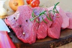 Carne rossa affettata sul bordo di legno con le erbe e le spezie Immagine Stock