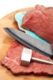 Carne rossa luminosa fresca del manzo e un martello di legno per battere carne su un tagliere di legno leggero Bello e raggiro di fotografia stock