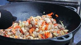 A carne saboroso, suculenta é fritada com os vegetais na bacia enorme e misturada com uma colher em um festival do alimento da ru filme