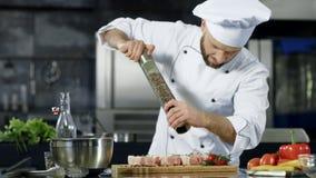Carne salpicando do cozinheiro chefe masculino na cozinha Bife salpicando do cozinheiro chefe do close up no local de trabalho vídeos de arquivo