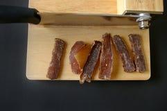 Carne secada cecina con la cortadora fotografía de archivo
