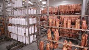 Carne secada, salchichas, productos de carne que cuelgan en el almacenamiento de la fábrica de la comida almacen de metraje de vídeo