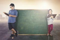 Carne sem gordura de dois estudantes com quadro vazio Imagens de Stock Royalty Free