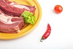 Carne sin procesar en una placa con una ensalada del tomate y de la pimienta Fotos de archivo