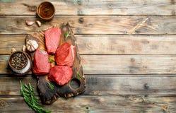 Carne sin procesar Pedazos cortados de carne de vaca con las especias y las hierbas fotografía de archivo libre de regalías