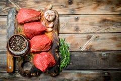 Carne sin procesar Pedazos cortados de carne de vaca con las especias y las hierbas imágenes de archivo libres de regalías