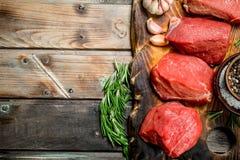 Carne sin procesar Pedazos cortados de carne de vaca con las especias y las hierbas fotografía de archivo