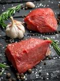 Carne sin procesar Pedazos cortados de carne de vaca con las especias y las hierbas en un tablero de madera imagen de archivo libre de regalías