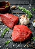 Carne sin procesar Pedazos cortados de carne de vaca con las especias y las hierbas en un tablero de madera foto de archivo libre de regalías