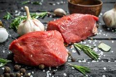 Carne sin procesar Pedazos cortados de carne de vaca con las especias y las hierbas en un tablero de madera fotos de archivo