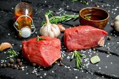 Carne sin procesar Pedazos cortados de carne de vaca con las especias y las hierbas en un tablero de madera imágenes de archivo libres de regalías