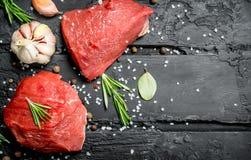 Carne sin procesar Pedazos cortados de carne de vaca con las especias y las hierbas en un tablero de madera foto de archivo