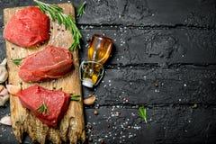 Carne sin procesar Pedazos cortados de carne de vaca con las especias y las hierbas en un tablero de madera imagenes de archivo