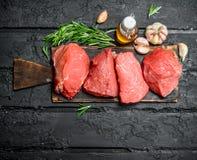 Carne sin procesar Pedazos de carne de vaca con ajo y romero imagen de archivo