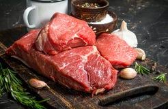 Carne sin procesar Pedazos de carne de vaca con las especias y las hierbas en un tablero de madera imagen de archivo libre de regalías