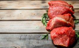 Carne sin procesar Pedazos de carne de vaca con las ramas del romero foto de archivo