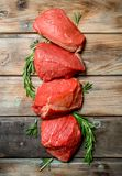 Carne sin procesar Pedazos de carne de vaca con las ramas del romero imagenes de archivo