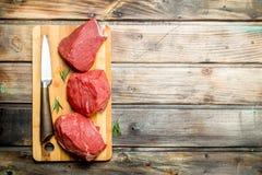 Carne sin procesar Pedazos de carne de vaca con un cuchillo foto de archivo