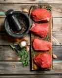 Carne sin procesar Pedazos de carne de vaca fresca con las especias y las hierbas foto de archivo
