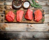 Carne sin procesar Pedazos de carne de vaca fresca con las especias y las hierbas fotos de archivo