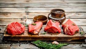 Carne sin procesar Pedazos de carne de vaca fresca con las especias y las hierbas imagen de archivo libre de regalías