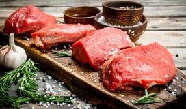 Carne sin procesar Pedazos de carne de vaca fresca con las especias y las hierbas fotografía de archivo