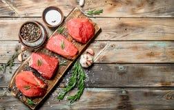 Carne sin procesar Pedazos de carne de vaca fresca con las especias y las hierbas imagen de archivo
