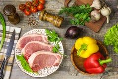 Carne sui pomodori di un piatto, aglio, cipolle, peperoni dolci, tavola calda e di legno Verdi del tovagliolo del coltello, barba Immagini Stock Libere da Diritti