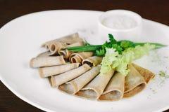 Carne suina affettata con lattuga sul piatto bianco in ristorante fotografia stock libera da diritti