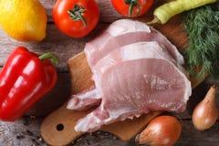 Carne suina cruda su un tagliere e su una vista superiore degli ortaggi freschi Fotografie Stock Libere da Diritti
