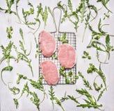 Carne suina cruda sulla griglia per la torrefazione sul fuoco con le erbe, rucola, vista superiore del fondo rustico di legno deg Fotografia Stock