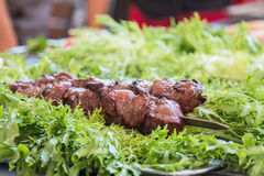 Carne suina fritta su fuoco e sulle erbe fresche Fotografia Stock