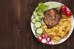 Carne suina sulla griglia con le patate e gli ortaggi freschi fritti su un piatto bianco Fotografie Stock