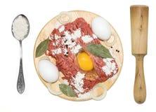 Carne tritata con le uova, il matterello ed il cucchiaio su un bordo Immagine Stock