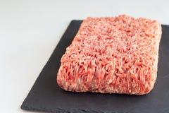 Carne tritata da carne di maiale e da manzo, carne macinata sul bordo scuro dell'ardesia, orizzontale, spazio della copia fotografia stock